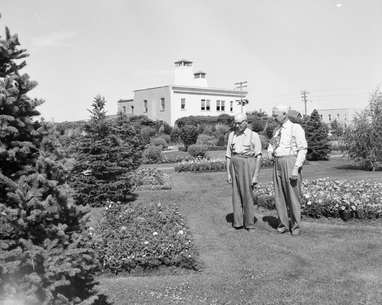 Two men standing in City Hall Park in the 1950s.