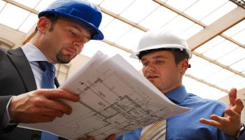Two men in hard hats looking at blueprints