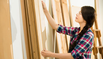 Photo of woman putting up plywood boards