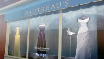 Painted mural of dresses hanging in a store front window.