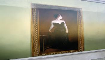 Painted mural of a framed painting of a slim woman standing beside a round table in a long black evening dress.