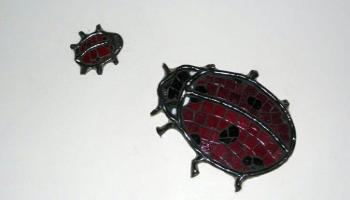 Glass mosiac tiles in the shape of two lady bugs, one big and one little on a wall.