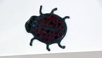 Glass mosiac tiles in the shape of a lady bug over a door frame