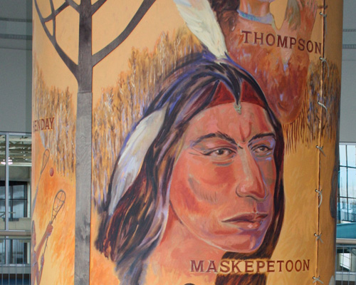 Close up of a painted canvas depicting aboriginal life. Portrait of a Maskepetoon.