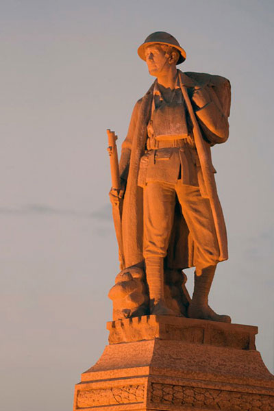 Photograph of the cenotaph of Major Frank Norbury taken at sunset. He is dressed in soldier apparel from the First World War.