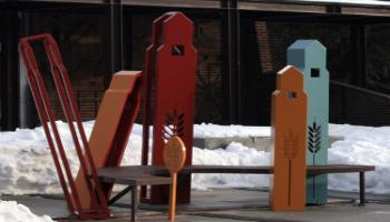 A bench sculpture with grain elevators for supports.