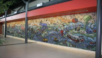 Wall sculpture highlighting iconic Red Deer, showcased in clay and glass mosaic, shows our architecture, our park spaces, our flora and fauna in a playful scene of flowers, birds, leaves, rabbits, ducks, bees, moose, fox, heron, and the occasional cyclist, rafter and kite flyer.