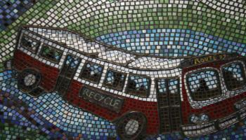 Close up showing a Red Deer City bus that is part of wall sculpture shomade of clay and glass .