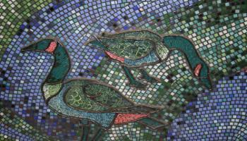 Close up showing ducks that are part of wall sculpture shomade of clay and glass .