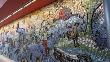 Close up of a wall sculpture out of colorful clay and glass showing images of children, buses, the Red Deer Water Tower and many others.