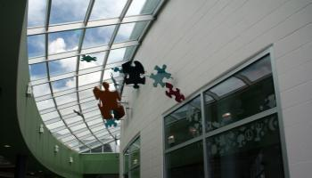 Picture of sculptures of different color puzzle pieces hanging from the roof in the G.H. Dawe Centre.