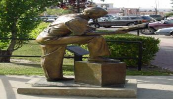 Side view of the sculpture of Francis Wright Galbraith, who is leaning his arm on his knee reading the newspaper and drinking a coffee.