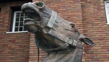 Close up of the horses head of the bronze sculpture of a horse-drawn wagon used by the fire brigade.