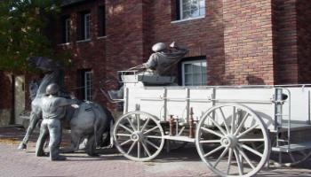 Rear-side view of the bronze sculpture of a horse-drawn wagon used by the fire brigade.