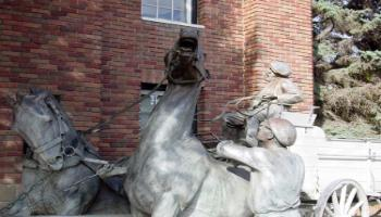Close up of the front of the bronze sculpture of a horse-drawn wagon used by the fire brigade.