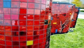 Side view of the red side of a rectangle sculpture made up of glass tiles an the photo etched tiles that show police and emergency services personnel and and out-reading hands trying to join. The word