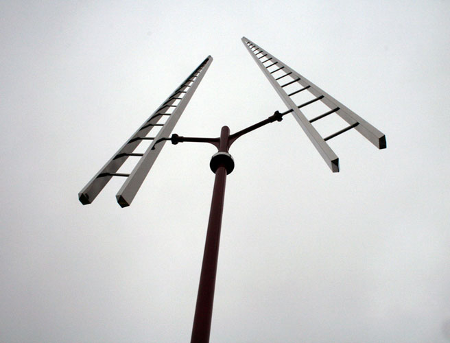 Sculpture of two ladders balanced at the top of a red pole.