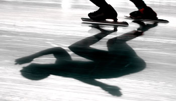 Photo of speed skater's skates and the shadow of the skater